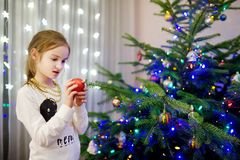 Adorable little girl decorating the Christmas tree with colorful glass baubles. Trimming the Christmas tree. Stock Image
