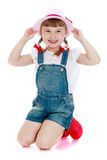 Adorable little girl in denim overalls and a hat Royalty Free Stock Photography