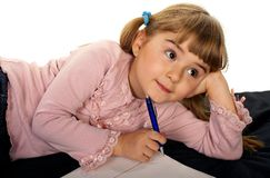 Adorable little girl doing homework. Adorable little girl thinking what to write royalty free stock photography