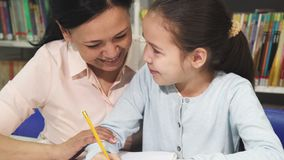 Adorable little girl doing homework with her mother. Close up of a cute little girl smiling happily writing in her notebook doing homework with her mother stock video footage