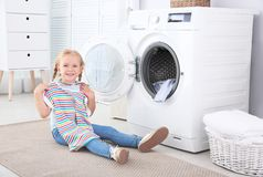 Adorable little girl doing laundry. At home royalty free stock images