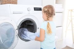 Adorable little girl doing laundry. At home stock photo