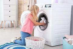 Adorable little girl doing laundry. At home stock photos