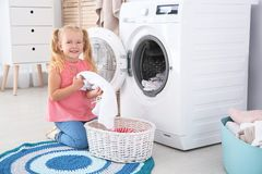 Adorable little girl doing laundry. At home stock photography