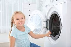 Adorable little girl doing laundry. At home stock images