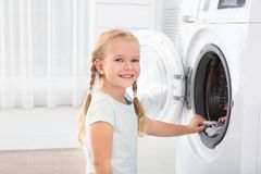 Adorable little girl doing laundry at home. Space for text stock photography