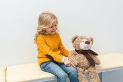 Adorable little girl doing neurology examination of teddy bear while sitting. On sofa stock photos