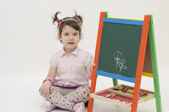 Adorable little girl draw two flowers on black board with chalk. Isolated on white background Royalty Free Stock Photos