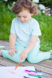Cute toddler girl drawing with felt-tip pens. royalty free stock image