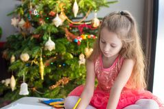 Adorable little girl drawing near Christmas tree Stock Images