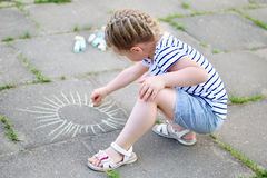 Adorable little girl drawing outside with chalk. At spring Royalty Free Stock Image