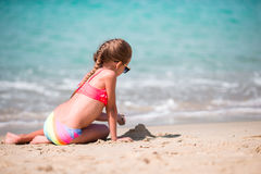 Adorable little girl drawing on sand at beach during summer vacation. Adorable little girl at beach during summer vacation Stock Photos