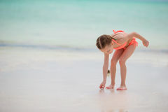 Adorable little girl drawing on white sand at the beach Royalty Free Stock Image