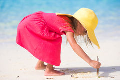 Adorable little girl drawing on white sand at the Royalty Free Stock Photography