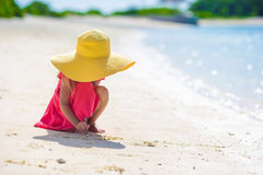 Adorable little girl drawing on white sand at the Royalty Free Stock Images