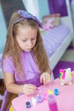 Adorable little girl draws paint in the room Royalty Free Stock Photos