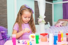 Adorable Little girl draws paints at her table in Royalty Free Stock Photos