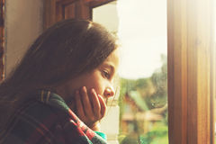 Adorable little girl dream in cold sunny morning. Stock Image