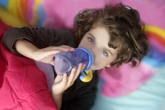 Adorable little girl drinking bottle Stock Image