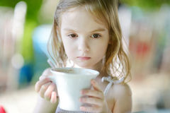Adorable little girl drinking hot chocolate Stock Photo