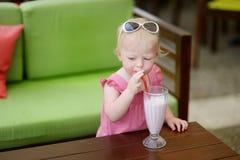 Adorable little girl drinking milkshake Stock Photography
