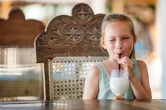 Adorable little girl drinking milkshake. Portrait of adorable little girl drinking milkshake Royalty Free Stock Image