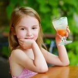 Adorable little girl drinking orange juice Royalty Free Stock Photo