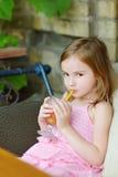 Adorable little girl drinking orange juice Stock Images