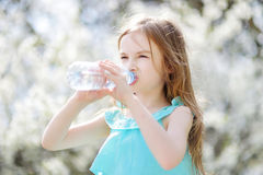 Adorable little girl drinking water on hot day Stock Photo