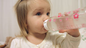 Adorable little girl drinks water from a bottle Stock Photo