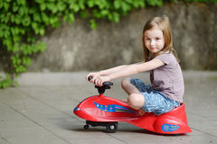 Adorable little girl driving a toy car Stock Images