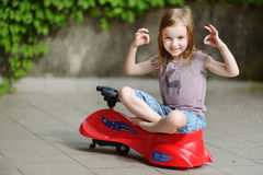 Adorable little girl driving a toy car. Outdoors on beautiful summer day Stock Image