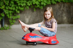 Adorable little girl driving a toy car. Outdoors on beautiful summer day Stock Photos