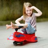 Adorable little girl driving a toy car Royalty Free Stock Photography