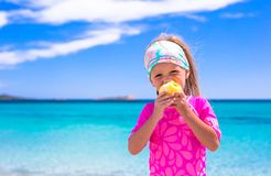 Adorable little girl eat apple at tropical beach Royalty Free Stock Photo
