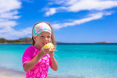 Adorable little girl eat apple at tropical beach Stock Photo