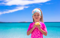 Adorable little girl eat apple at tropical beach Royalty Free Stock Images