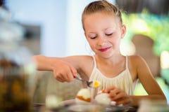 Little girl eating breakfast. Adorable little girl eating boiled egg for a breakfast in home or restaurant Royalty Free Stock Photo