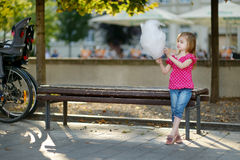 Adorable little girl eating candy-floss outdoors Stock Photography