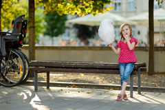 Adorable little girl eating candy-floss outdoors Stock Image