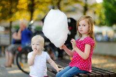 Adorable little girl eating candy-floss outdoors Royalty Free Stock Images