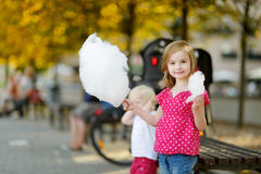 Adorable little girl eating candy-floss outdoors Stock Images