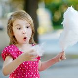 Adorable little girl eating candy-floss outdoors Royalty Free Stock Photos