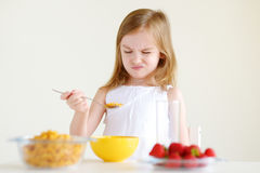 Adorable little girl eating cereal in a kitchen Stock Photos
