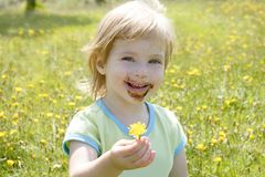 Adorable little girl eating chocolate. Outdoor field Royalty Free Stock Photos