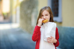 Adorable little girl eating fresh baked bun on warm and sunny summer day Royalty Free Stock Photos