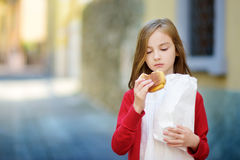 Adorable little girl eating fresh baked bun on warm and sunny summer day in Toscolano-Maderno town Stock Image