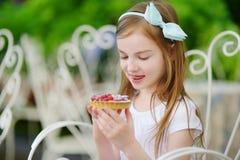 Adorable little girl eating fresh strawberry cake Stock Image