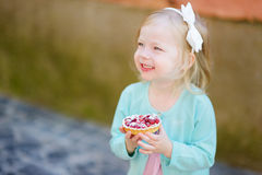 Adorable little girl eating fresh strawberry cake Royalty Free Stock Image