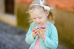 Adorable little girl eating fresh strawberry cake Stock Photo
